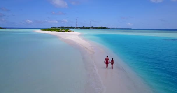 Lovely young couple enjoying vacation on coastline of tropical sandy beach, travel concept video
