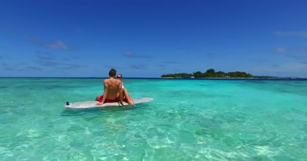 Young man and woman swim on surfboard in sea. Beautiful couple resting on tropical resort