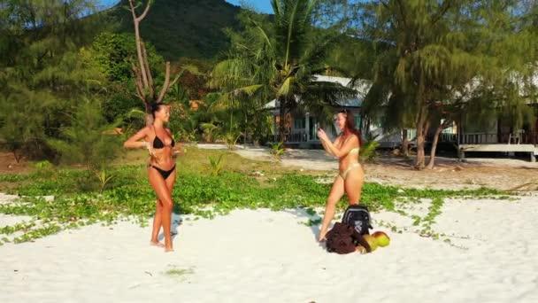 Két fiatal barátnő bikiniben a homokos tengerparton. Egy lány fotózza a barátnőjét mobilon. Gyönyörű nők pihennek trópusi üdülőhelyen