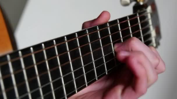 Brnká, hrál na akustickou kytaru
