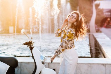 Spectacular brown-haired girl with excited smile posing with white scooter waiting for ride in sunny day. Portrait of charming young woman in glasses and elegant attire gladly posing near fountain..