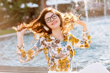 Cheerful elegant lady playing with her curly hair and enjoying life in sunny day. Attractive girl in glasses and stylish shirt chilling while listening music and resting on city fountain in morning..
