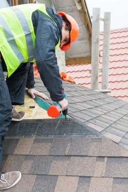 worker dismantling roof shingles