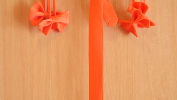 orange bow tie and necktie on wooden backgrond