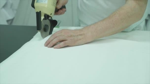 Vágás egy darab ronggyal a divat stúdió asztalnál nő.