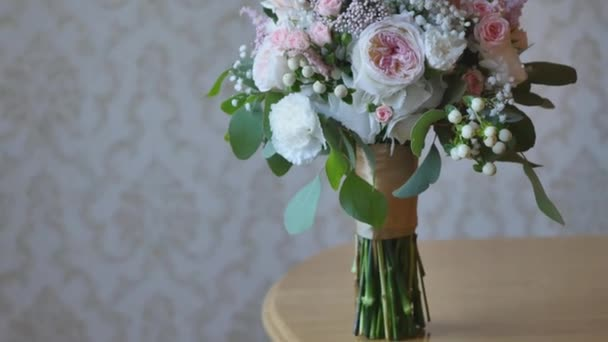 Wedding bouquet of bride - colorful flowers pink, white roses and yellow freesia lying on table at wedding.