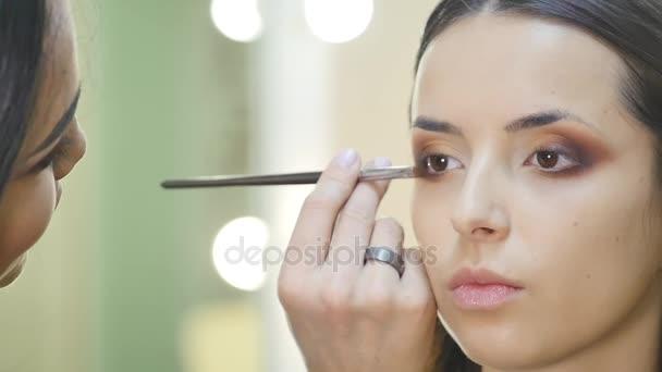zblízka portrétní krásná mladá bruneta žena vyrovnávací oko zóny tvoří s kosmetické štětce