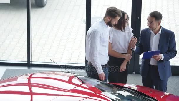 Pohled shora mladých mužů konzultant a kupující podpisem smlouvy pro nové auto v autosalónu. Koncept pro pronájem vozu