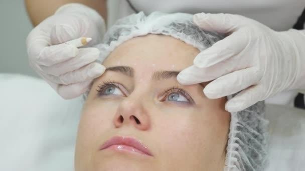 Doktor nakreslení čar označeného pacienta tvář pro obličejové plastické chirurgie na klinice