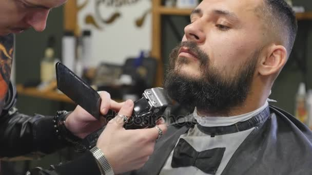 Detail pohledný mladý vousatý muž dostává vousy péče v moderní holičství