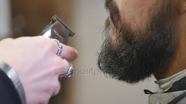Detail pohledný mladý vousatý muž dostává vousy péče v moderní holičství.