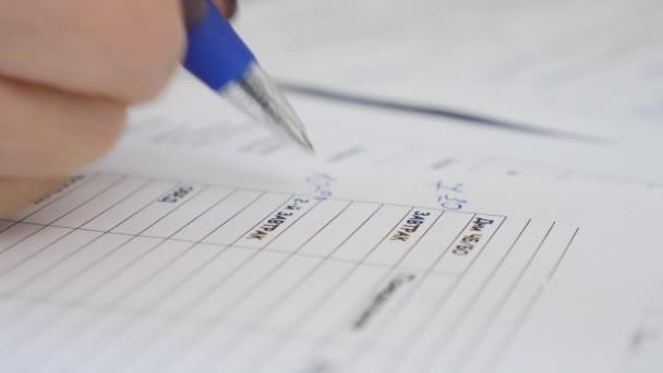 Makroaufnahme einer Hand beim Schreiben eines Dokuments auf Papier mit einem Federhalter.