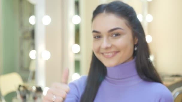 S úsměvem šťastná žena vzdává palce, schválení a úspěch nebo signál hlasování, zaměření na ruku