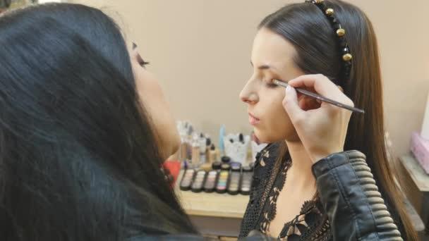Make-upu. Žena Make-up použití zblízka. Tužka na oči. Kosmetické Eyeshadows. Úrovní očí štětec na Make-upu. Krásy dívka s dokonalou pletí. Řasy. Hnědé oči. Makeover