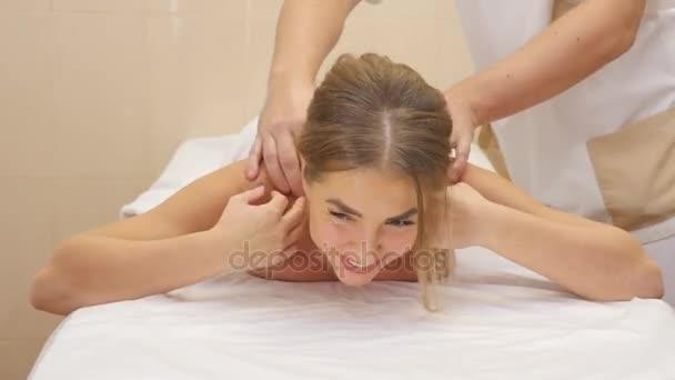 Krásná blondýnka se dívá na kameru a usměvavý, ležící na frontě a masážní terapeut je masírovat ji zpět