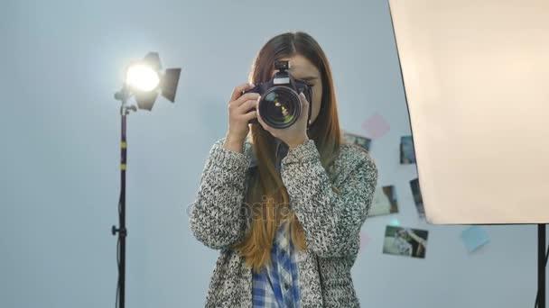 junge Fotografin mit Kamera im professionell ausgestatteten Studio