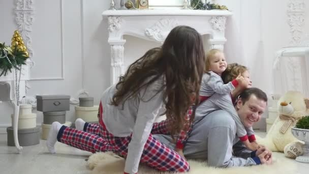 Christmas Pajamas Photoshoot.Happy Young Family Sitting On Floor At Christmas Morning In Pajamas Smiling Photoshoot With Flash Light