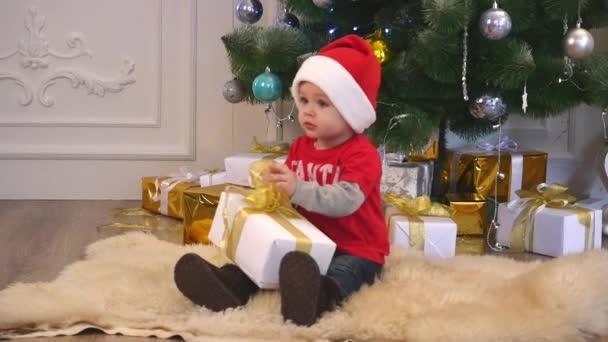 roztomilý chlapec v santa čepice a motýlek vázací stuha na dárek