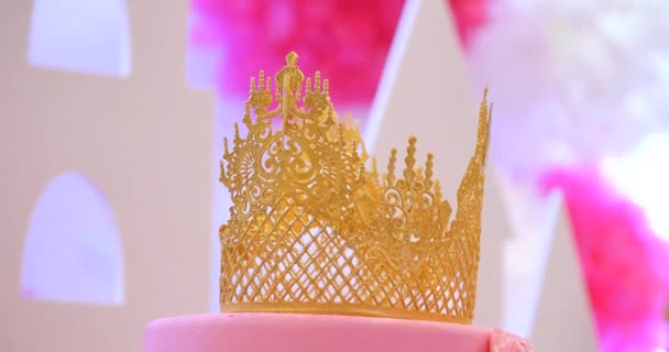 Delicious tiered pink wedding cake decorated with crowns