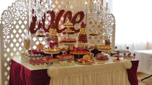 Candy bar, red colour, marsala. Table with wedding cake, sweets, candies, dessert, pops.
