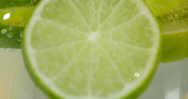 grüner Kalk mit Wasserspritzer isoliert auf weißem Hintergrund