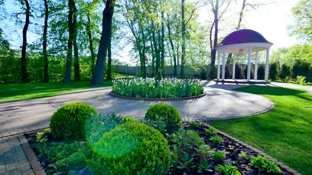 zelený dvůr s altánem a květinové záhony