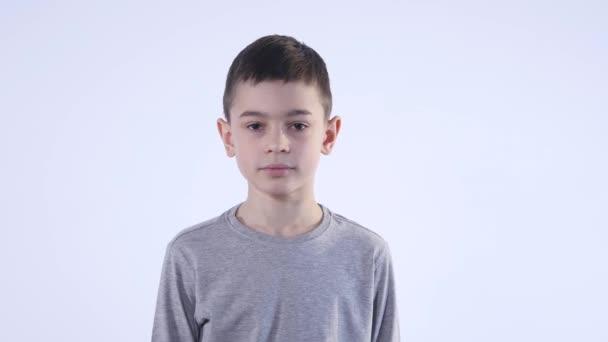 A fiú csodálkozott, szürke háttér portré