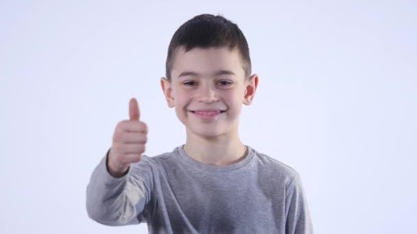Lächelnder Junge, der seinen Daumen isoliert auf dem weißen Hintergrund hochhält