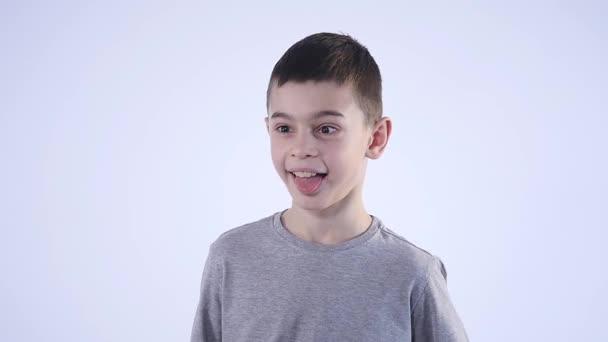 Aranyos kisfiú, hogy vicces arcok, fehér háttér