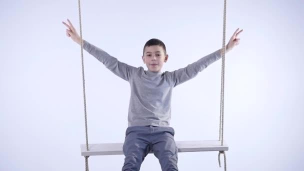 Radostné chlapeček houpat na houpačce a ukázal štěstí izolovaných na bílém pozadí
