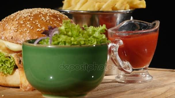 Rotující hamburger s kečupem vylije hranolky a salátem. Černé pozadí Hamburger s hranolky a salátem