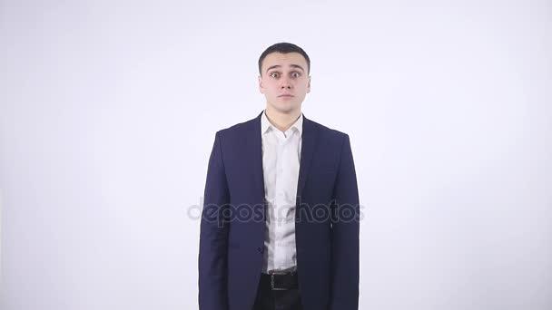 Hombre con traje y las manos en la cabeza con gesto sorprendido aislado  sobre fondo blanco