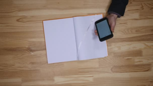 man planning To do list with smartphone calendar and notepad, top view