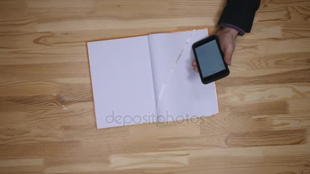 muž v úmyslu udělat seznam kalendáře z telefonu a Poznámkový blok, pohled shora