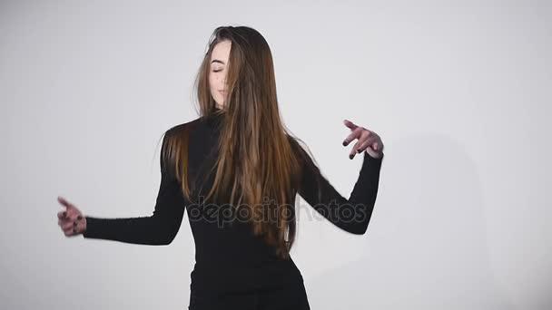 Mladé krásné kavkazských dívka vlající vlasy a hlavu na bílém pozadí v slowmotion