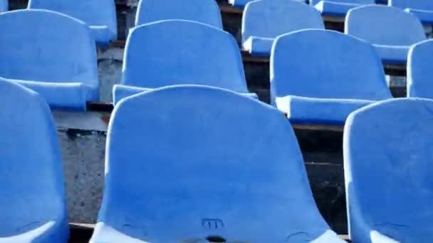 blaue Plastiksitze im Stadion, Kamera schiebt sich nach links. Abstrakt