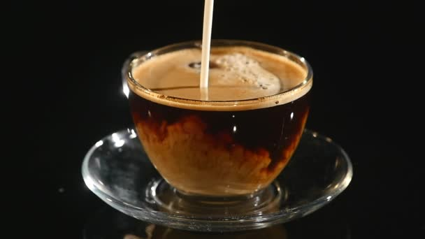 Pouring milk in cup of coffee, closeup slow motion