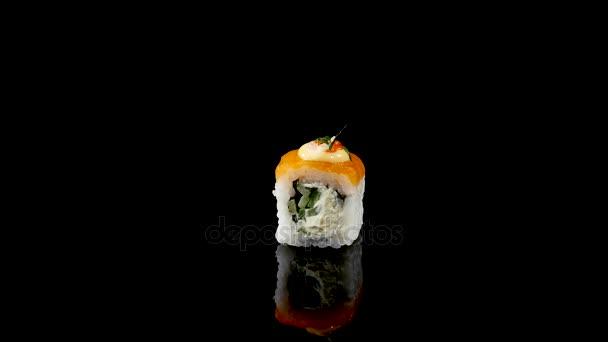 sushi tekercs lazac és kaviár a fekete háttér forgó