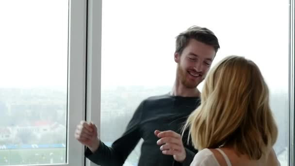 krásný mladý pár při pohledu z okna s úsměvem na tváři