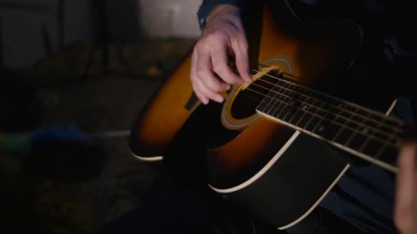 muž hraje na kytaru zblízka