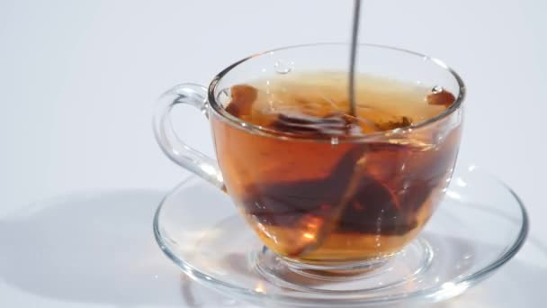 Muž míchání čaj s lžičku ve sklenici