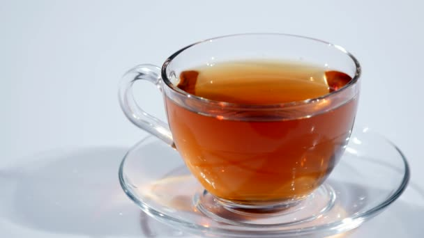 In a cup on a saucer with black tea falls a slice of lemon on a white background, slow mo