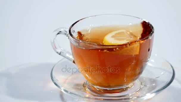 Šálek na podšálku s černého čaje spadá plátkem citronu na bílém pozadí, pomalé mo