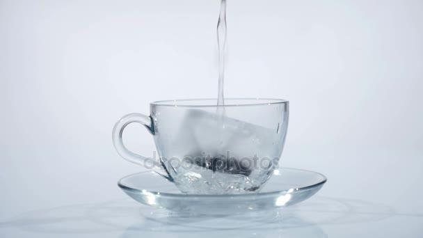 Čajový sáček ve skleněném pohárku je plná horké vody na čaj. Zpomalený pohyb
