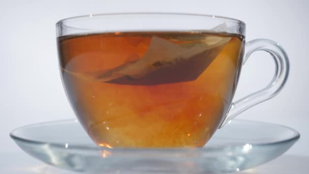 Man stirring tea with spoon in glass cup