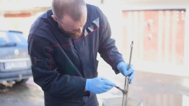 Autószerelő mérnök dolgozik a műhelyben szolgáltatás autó lengéscsillapító