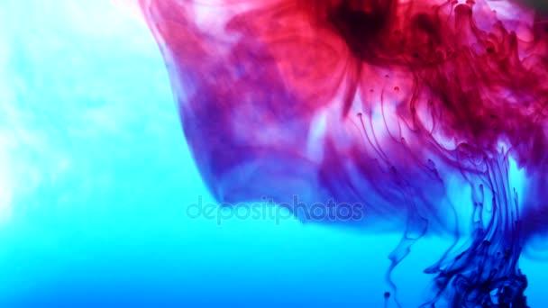 Světlé barevné pozadí modrá a červená kapalina inkoustové barvy, míchání ve vodě