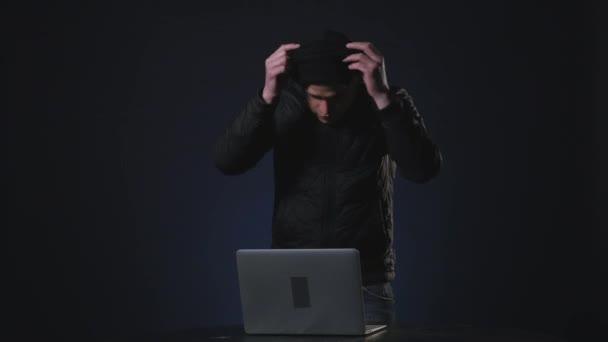 mladý muž zloděj krade data z počítače