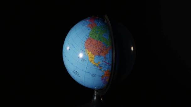 Közelkép a fekete háttér forgó földgömb