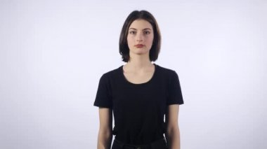 Young woman making do not know sign on white background